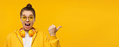 istock Horizontal banner of young excited girl wearing hoodie, glasses and wireless headphones around neck, pointing right to copy space, isolated on yellow background 1252905222