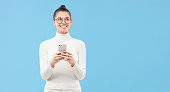 istock Horizontal banner of young student girl in glasses, looking aside with smile as if dreaming with smartphone in hands, isolated on blue background with copy space 1227242570