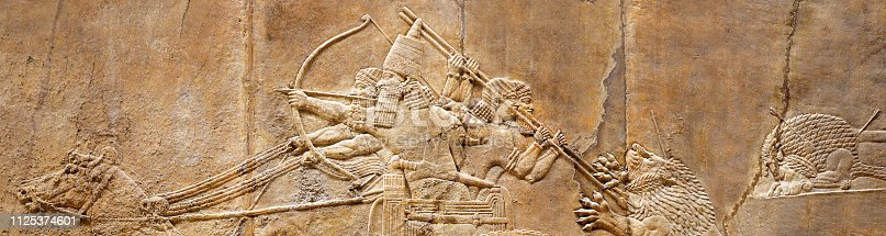 Assyrian wall relief of the royal lion hunt. Ancient carving panoramic panel from Middle East history. Remains of the culture of ancient civilization. Horizontal banner with Assyrian and Sumerian art.