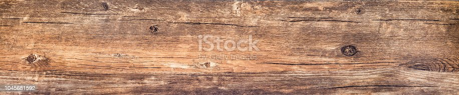 Wood texture background. Rustic rough wooden plank with nature color and pattern. Old knotted long board of wood close-up. Horizontal banner with vintage wood texture.