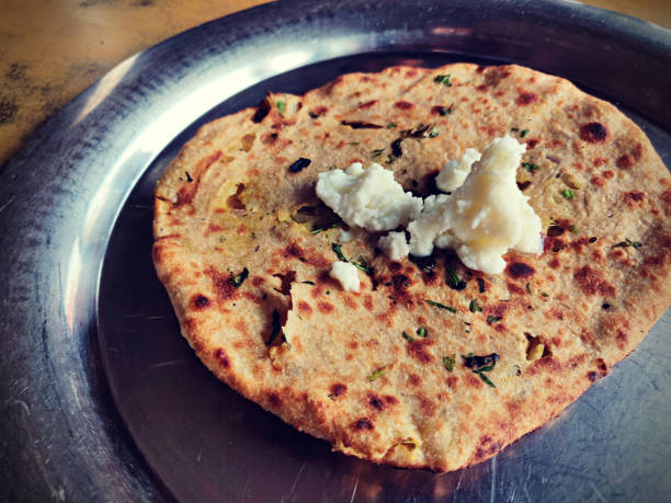 Horizontal click of crispy Amritsari Aloo-Paratha, kulcha stuffed with potato, onion, green dhaniya and spices with white butter makkhan served in a steel plate or thali. stock photo