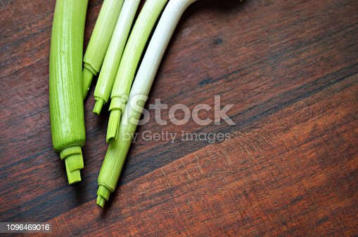 923629650istockphoto Horizontal click of garlic stalks with bright light green color merging into white shade over a dark brown wooden board surface 1096469016