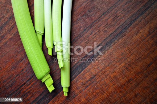 923629650istockphoto Horizontal click of garlic stalks with bright light green color merging into white shade over a a dark brown wooden kitchen board surface 1096469826