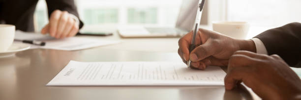 horizontale nahaufnahme schwarzer geschäftsmann sitzt am schreibtisch unterzeichnung vertrag - unterschreiben stock-fotos und bilder