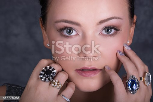 Horizontal colour studio shot on gray of young woman with big blue/gray eyes and many rings on both hands  touching cheek. hair back and up.