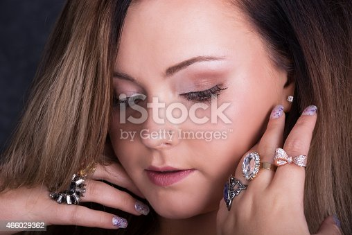 Horizontal closeup studio shot on gray of young woman, 18 years old, with subtle natural makeup. Looking down at hands close to face, wearing many crystal and rhinestone rings.