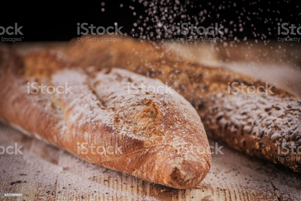 Horizontal closeup view of two fresh crunchy baguettes with raining flour on the rustic wooden desk stock photo