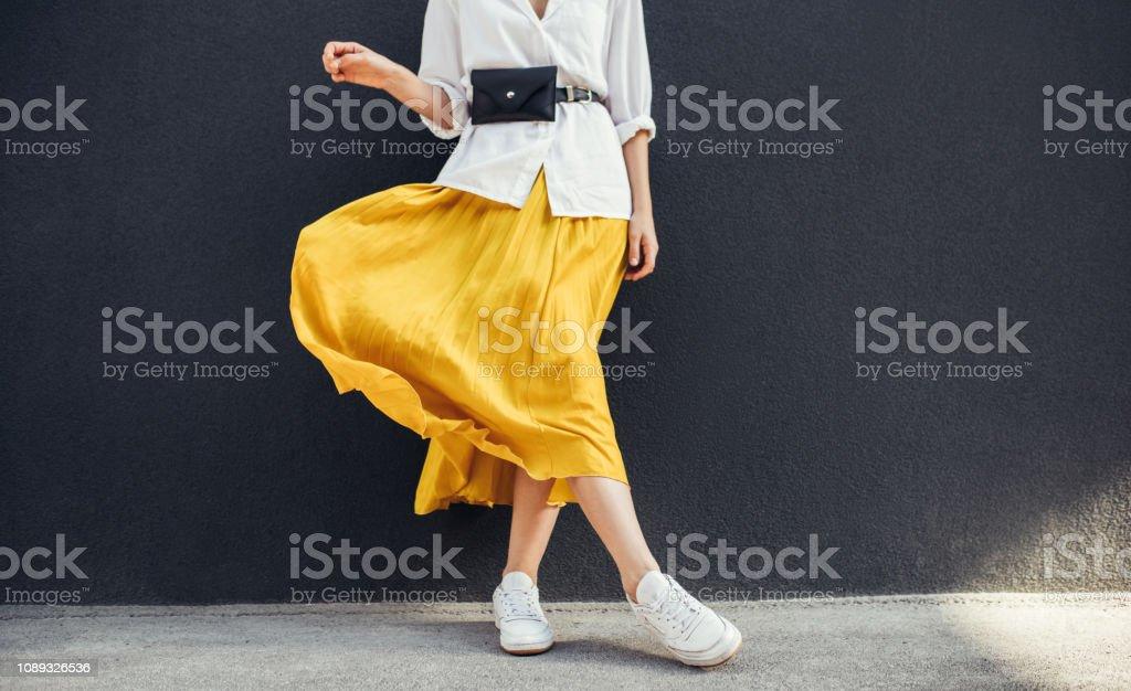 Horizontale bijgesneden beeld van stijlvolle slanke vrouw in mooie gele rok. Kaukasische vrouwelijke fashion model staande over grijze muur achtergrond buiten met kopie ruimte. - Royalty-free Been Stockfoto