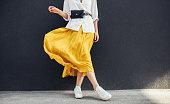水平方向は、美しい黄色のスカートでスタイリッシュなスリムな女性のイメージをトリミングしました。灰色の壁背景コピー スペースと屋外に白人女性のファッション モデル立ち。