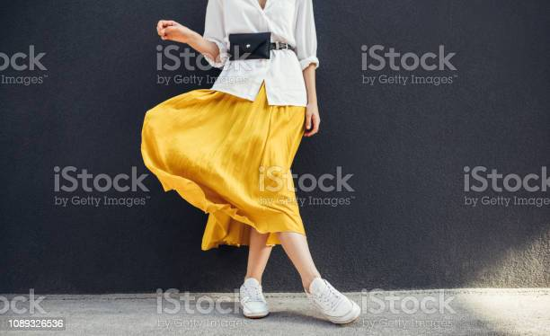 Horizontale Bijgesneden Beeld Van Stijlvolle Slanke Vrouw In Mooie Gele Rok Kaukasische Vrouwelijke Fashion Model Staande Over Grijze Muur Achtergrond Buiten Met Kopie Ruimte Stockfoto en meer beelden van Been