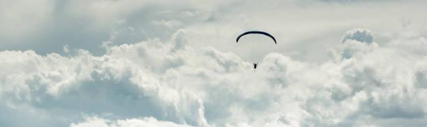 Horizontal geschnittene Bildgleitschirmflieger über wolkenverhangenem Himmel – Foto