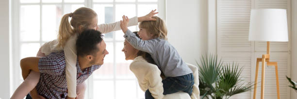 horizontal image cheerful parents piggybacking little children playing at home - banner web foto e immagini stock