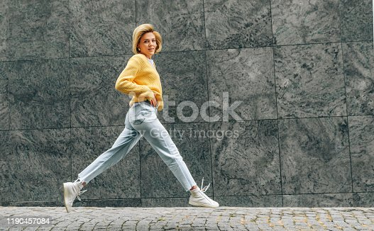 Horizontal image of cheerful young woman wearing yellow sweater, blue high waist jeans, jumping high, feeling happy on the city street. Student blonde female as joyful expression