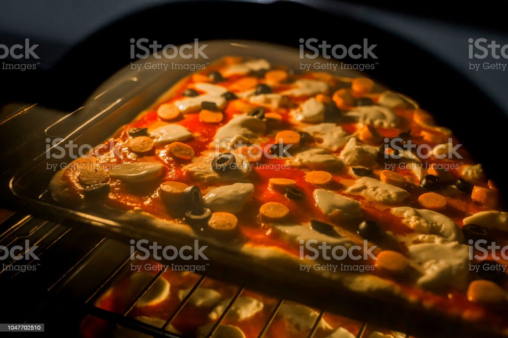 horizontal image of homemade pizzas while baking in the oven stock photo