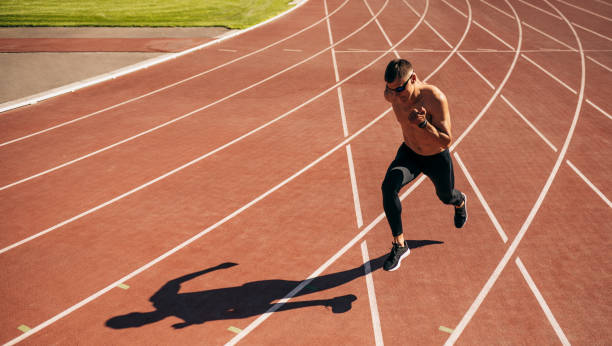 Horizontal image of young man athlete running on a track race in stadium. Athletic male jogging on a sunny day at stadium. People, healthy lifestyle and sport concept stock photo