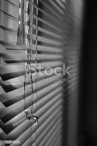 Horizontal metal jalousie with old rope. BW photo.
