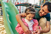 Horizontal outdoor image of cute daughter playing with her handsome father outdoors. Dad and little girl playing at playground together. Father and daughter share love. Daddy and his child outside.