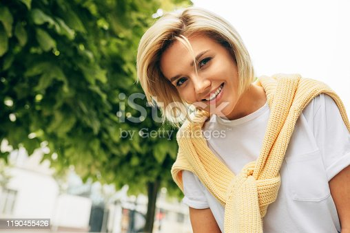 870648602 istock photo Horizontal outdoor portrait of happy young woman wearing white t-shirt and yellow sweater, smiling broadly and posing on the city street. Student female walking on the street, has joyful expression 1190455426