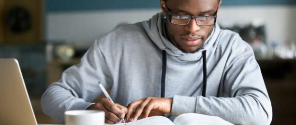 horizontal photo african student study writing using book and computer - esame università foto e immagini stock
