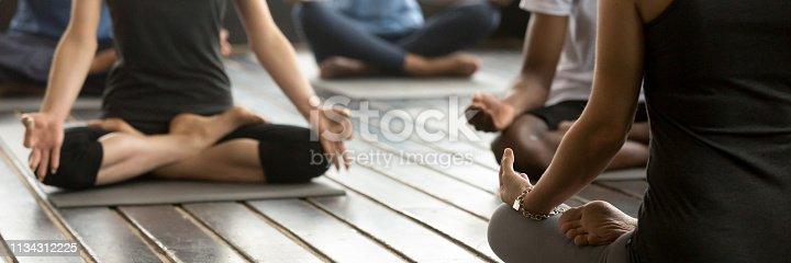 istock Horizontal photo group people sitting in lotus position practicing yoga 1134312225