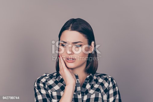 istock A horizontal photo of a young worried woman in checkered shirt suffering from strong toothache and touching her cheek 942799744