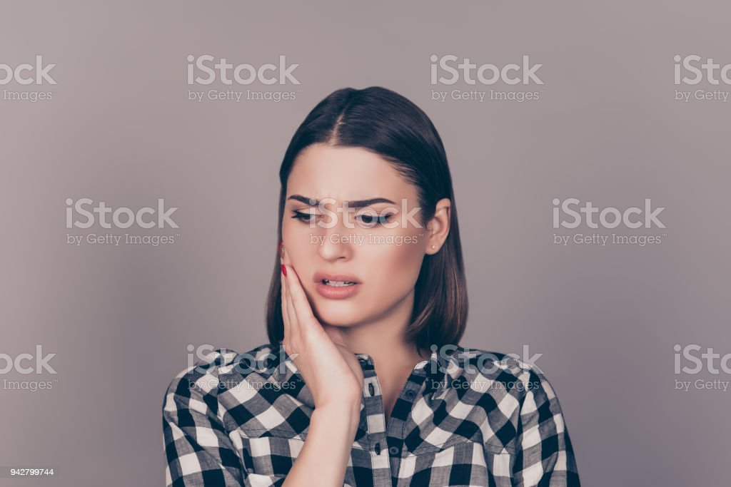 A horizontal photo of a young worried woman in checkered shirt suffering from strong toothache and touching her cheek stock photo