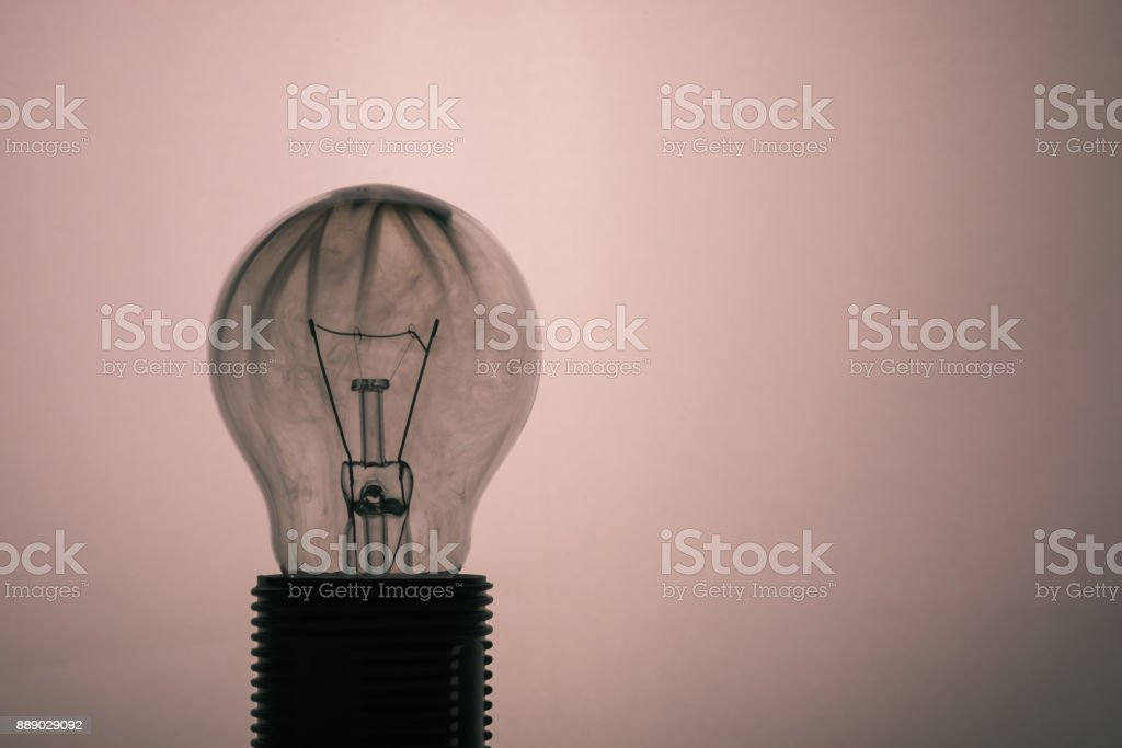 Horizontal photo of single glass bulb placed in the socket on light background. The grey smoke inside was caused by burning wire. The glass is dirty after the flames and fire. stock photo