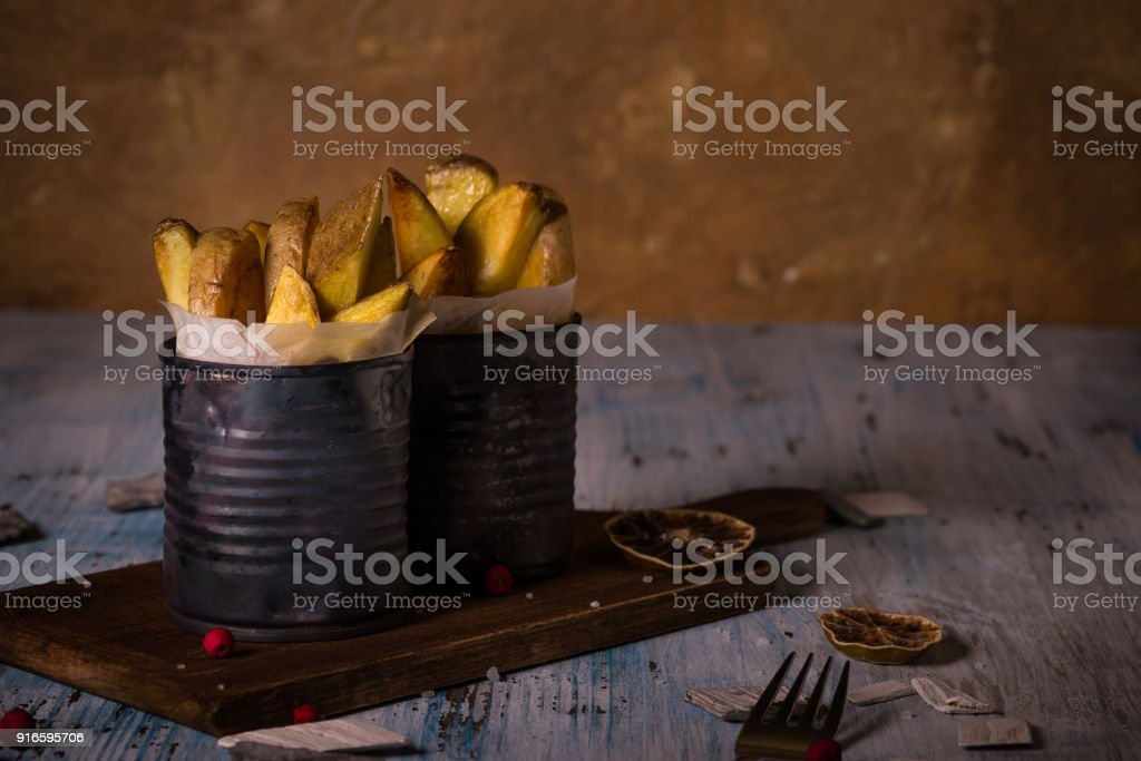 Horizontal photo of two portions of fried potato strips with skin. Homemade french fries are placed in old vintage cans with paper inside and on worn chopping board and blue table. stock photo