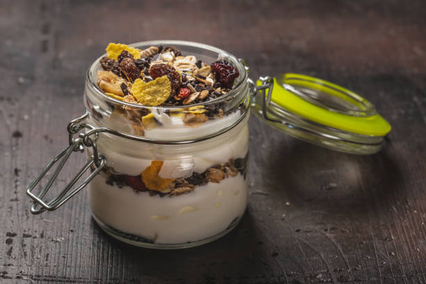 Horizontal photo of white yogurt. Yogurt is in small glass jar with metal lock and sealed cover. Muesli with dried food is layered in and on yogurt. Glass is placed on dark wooden board. stock photo
