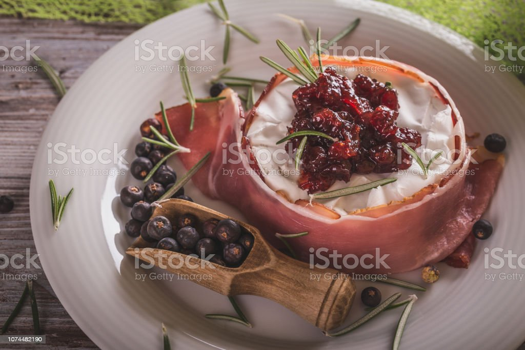 Horizontal photo of whole camembert. Cheese is wrapped in dry ham and has cranberries on top. Cheese is on white plate with spilled juniper fruit around on wooden board with worn color. stock photo