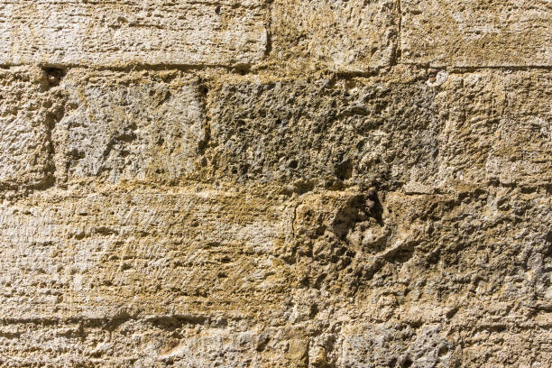 Horizontal photo with texture of typical wall in Tuscany Italy. The used stone is volcanic yellow tuf with holes and groves. stock photo