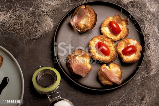 Horizontal photo with top view on black plate with several baked puff pastry cups. Cups are stuffed by cheese. Red tomatoes and dried ham is on pastries. Plate is on dark wooden board.