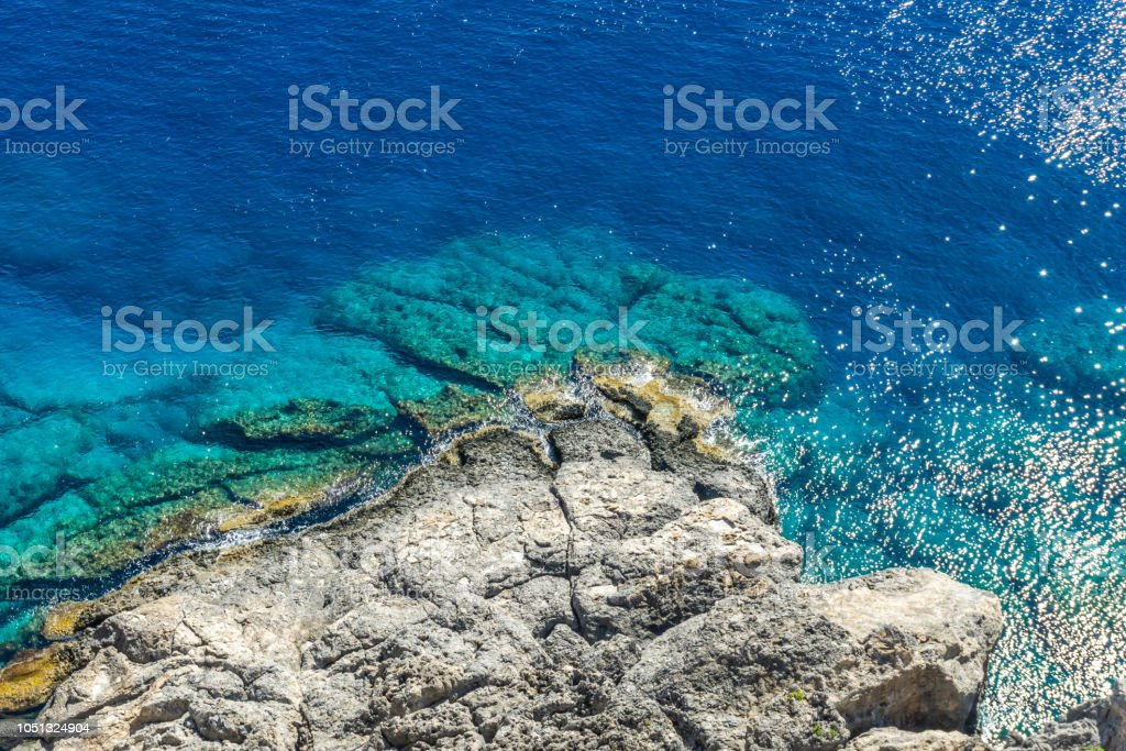 Horizontal photo with view down on rocky reef with blue sea around. Reef is under acropolis in Rhodos town Lindos captured in sunny summer day. stock photo