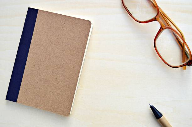A horizontal photograph of a brown cardboard bound notepad along with a brown and black color pen and spectacles placed aesthetically over a wooden look beige color background. stock photo