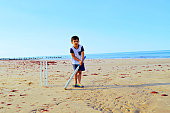 Playing or batting under pressure. A little Indian , Asian boy named Pranav Syal from India, stands or is standing on a sandy beach sideways to the camera, holding a cricket sport bat, resting it on the ground, holding it with his both the hands facing the camera, tired and stressed expressions. Off white colored cricket wickets stumps fixed or positioned on a sandy beach on wet sand behind the boy. There is red color seaweed or weeds over the sand too. The wet sand has foot prints or marks over it. Copy space. No text. The waves of the sea splash at the sandy coast. The blue sky merges or blends into the blue sea, both being in the same tone of colour and create a magical horizon. White color clouds can be seen in the sky. Beautiful natural landscape, scenic nature and people photography. The boy is in striped t shirt or stripe stripes shirt, the pocket and half sleeves in navy blue and carbon black denim cropped pants, or jeans material half pant and lime green and blue colour flip flop slippers, making him look like a casual sports person.  Head down, side pose. Suitable for IPL, Indian Premier League, World cup matches. Sharp long shadow. Bright picture. Wooden groyne in the sea. Boy in centre, middle, slightly towards the left.