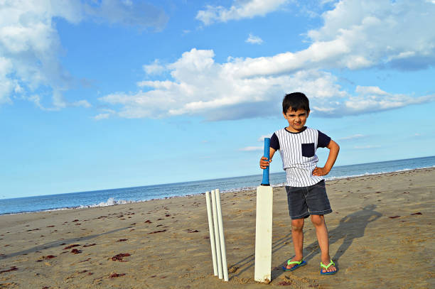 Horizontal photograph of a small boy standing on a beach holding a cricket bat and wickets by his side on a summer day. stock photo