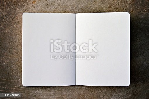 An empty blank, white color page of a notepad, placed over a wooden look background. No people. No text. Notepad placed open in the middle of the frame.