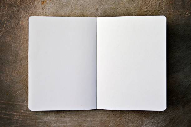 A horizontal photograph of a white plain page of a notepad along with a pair of spectacles placed aesthetically over a wooden look beige color horizontal background. stock photo