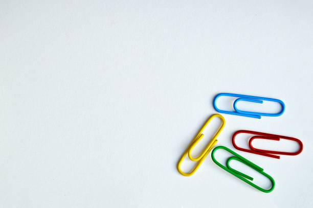 A horizontal photograph of four office paper clips over white background stock photo