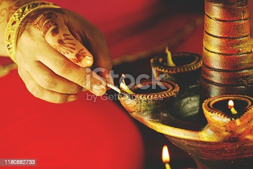 A tower or layers layer of lit diyas - concept of prayer and celebrations, symbol of peace and hope. Black background. A woman giving matchstick fire to one mitti diya, earthen lamps with oil and jyot or lau. Apt for Diwali, Deepawali, Durga pooja, Rakshabandhan, Raakhi, Ganesh Chaturthi Onam, greh pravesh, house warming, Inauguration, opening of an event, festival, festivals.  no text, copy space, copyspace. The woman has beautiful mehendi pattern. Nails painted in golden coloured nail paint and a jadau kada or kangan.