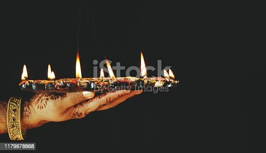 Diwali, deepawali greetings card, A circular plate of beautiful lit mitti diyas - concept of prayer and celebrations, symbol of peace and hope. Black background. A woman holding a pooka thaali, thali with fire, flames in wicks of  mitti diya, earthen lamps with oil and jyot or lau. Apt for Diwali, Deepawali, Durga pooja, Rakshabandhan, Raakhi, Ganesh Chaturthi Onam, welcome, Inauguration, opening of an event, festival, festivals. No people, no text, copy space, copyspace. Black background. The woman has beautiful mehendi pattern and a jadaau kangan on hand and wristb and arms. Greeting card