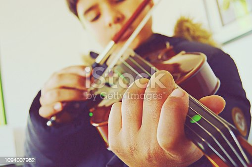 A boy playing the stringed and bowed musical instrument, the violin, captured from the front. Horizontal frame. Depth of field. The child is holding the violin bow in his one hand and is pressing it against the strings in a beautiful pose. Brown faux fur attached to the hood, hoodie of his dark blue black coat, jacket hangs behind his shoulders. The violin is secured under his chin.The boy and the violin cover the most of the frame and is center, centre aligned. Some empty off white copy space around the boy. Apt for Valentine / valentine's day, love greetings card, poster, sorry or Thank you, Propose, proposal message /  messages. No text. A wall hung artefact, picture, painting in the hindsight.