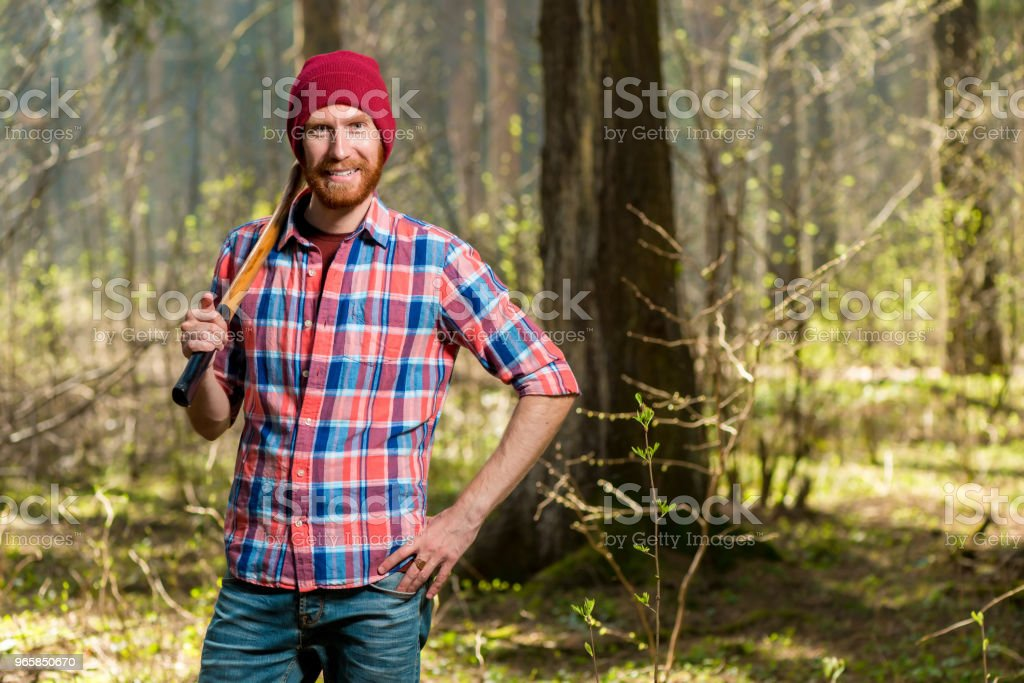 horizontal portrait of a forester with a beard in the forest with an ax - Royalty-free Adult Stock Photo