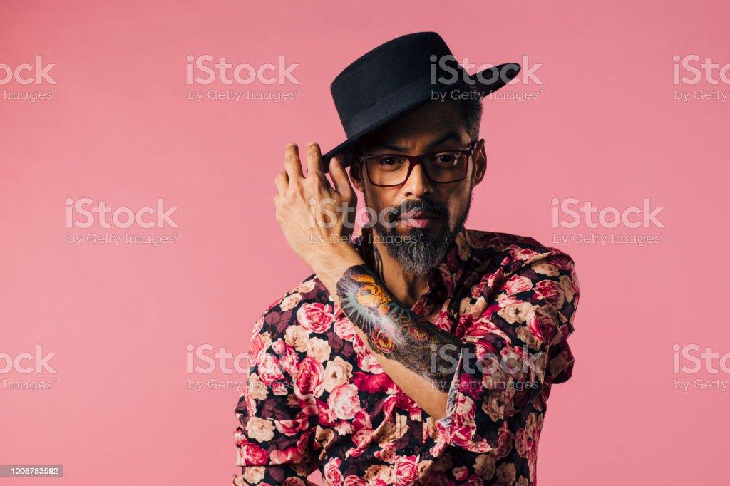 Horizontal retrato de un hombre muy cool con tatuajes, inclinando su sombrero - foto de stock