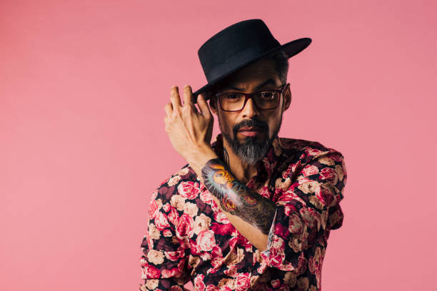 horizontale porträt eines sehr cool mit tattoos, seinen hut zu kippen - alte tattoos stock-fotos und bilder