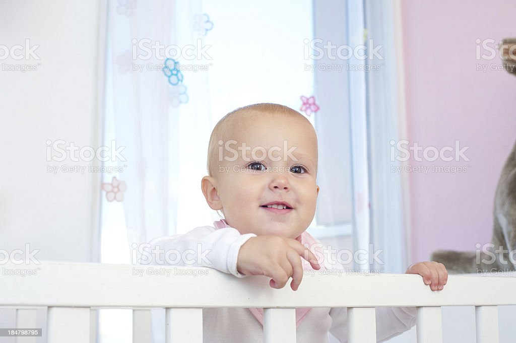 Horizontal portrait of an adorable baby smiling in crib royalty-free stock photo