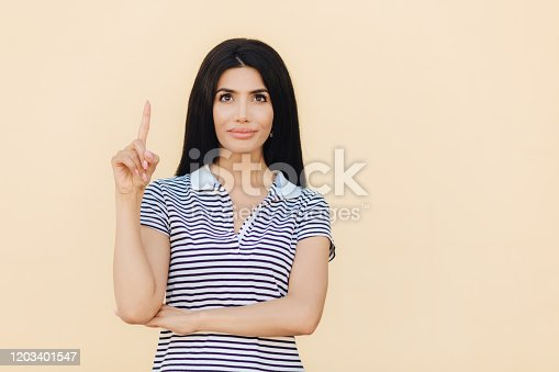 Horizontal portrait of attractive female with dreamy expression, has full lips and make up, wears casual striped t shirt, indicates with fore fingers upwards, shows blank space for your advertisement