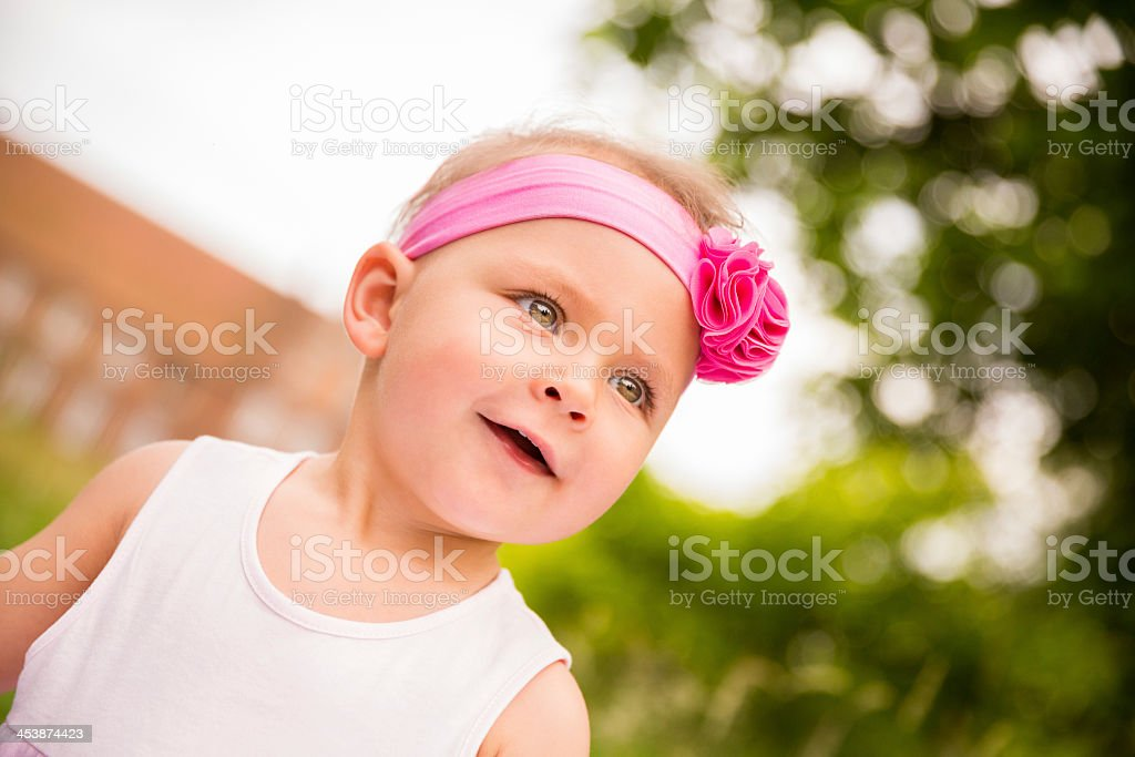 Horizontal portrait of baby girl in pink smiling royalty-free stock photo