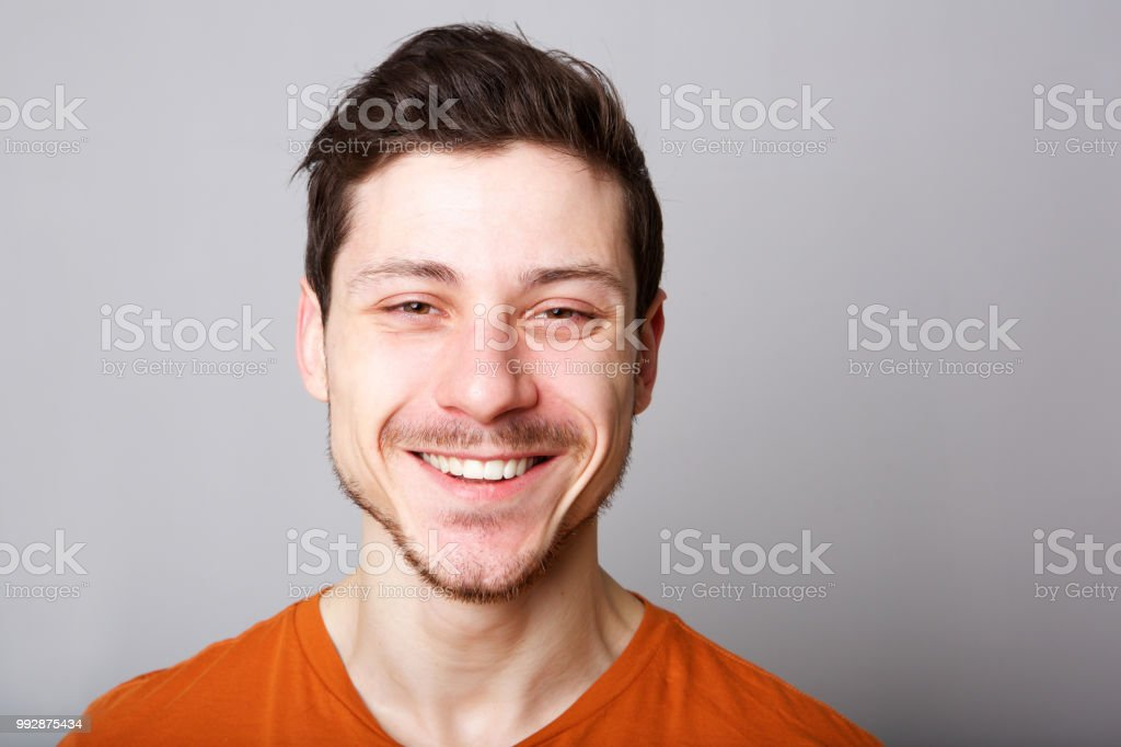 horizontal portrait of smiling young man against gray backgorund stock photo