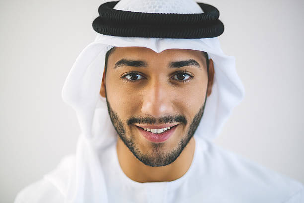 Horizontal Portrait of Young Smiling Arab Man Young man from United Arab Emirates is posing for a close-up portrait looking at the camera and smiling charmingly. Wearing traditional white clothing: kandura (also known as dish dash), agal and kaffiyeh. Dark brown eyes, black facial hair. Background of the image is light matte grey. Image was made in Dubai, United Arab Emirates. arabic style stock pictures, royalty-free photos & images
